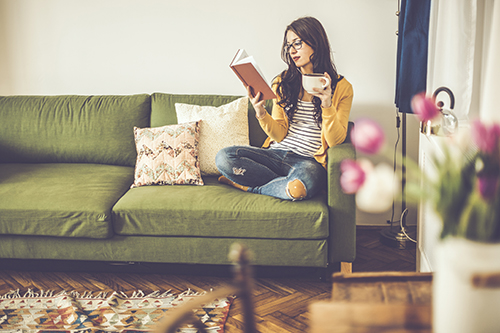 Woman reading on couch in living room
