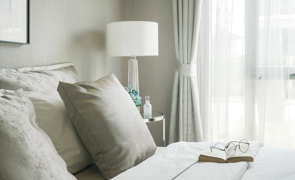 bedroom with reading glasses, book and lamp in very light room