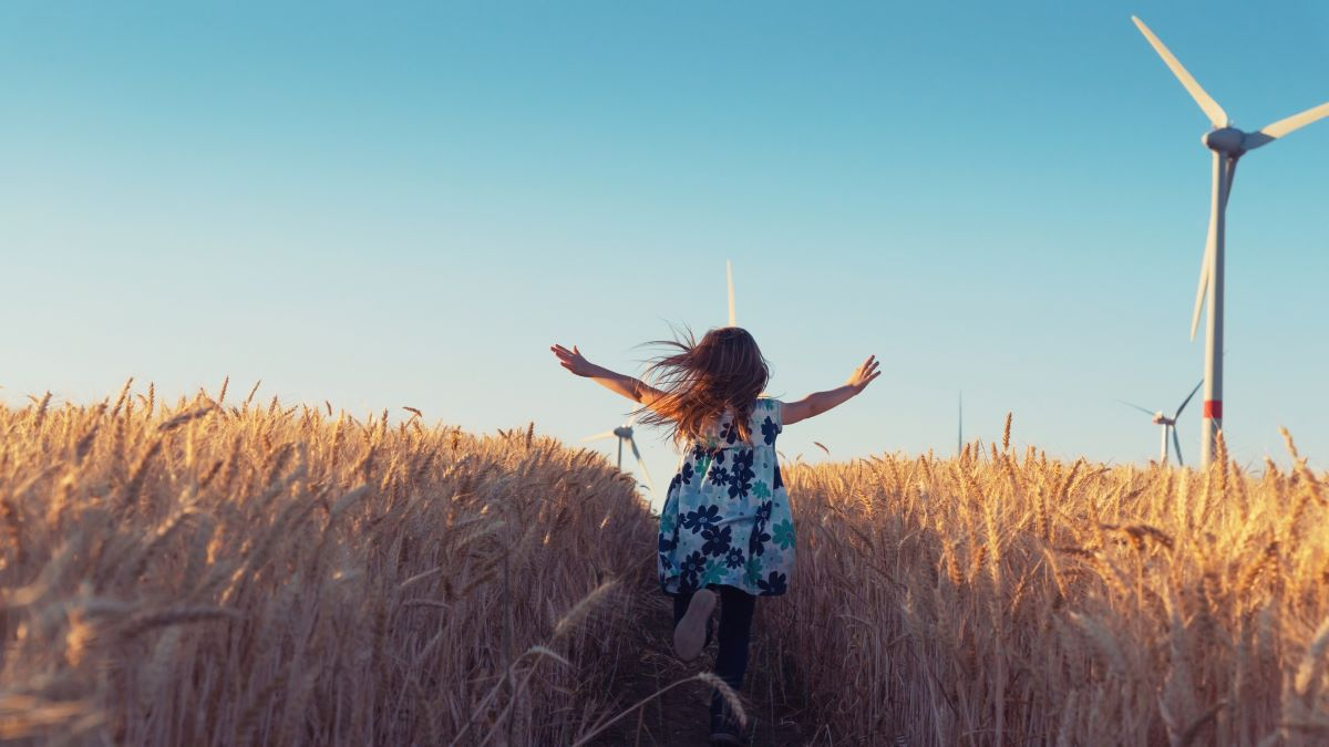 Girl running in a field towards a wind turbine