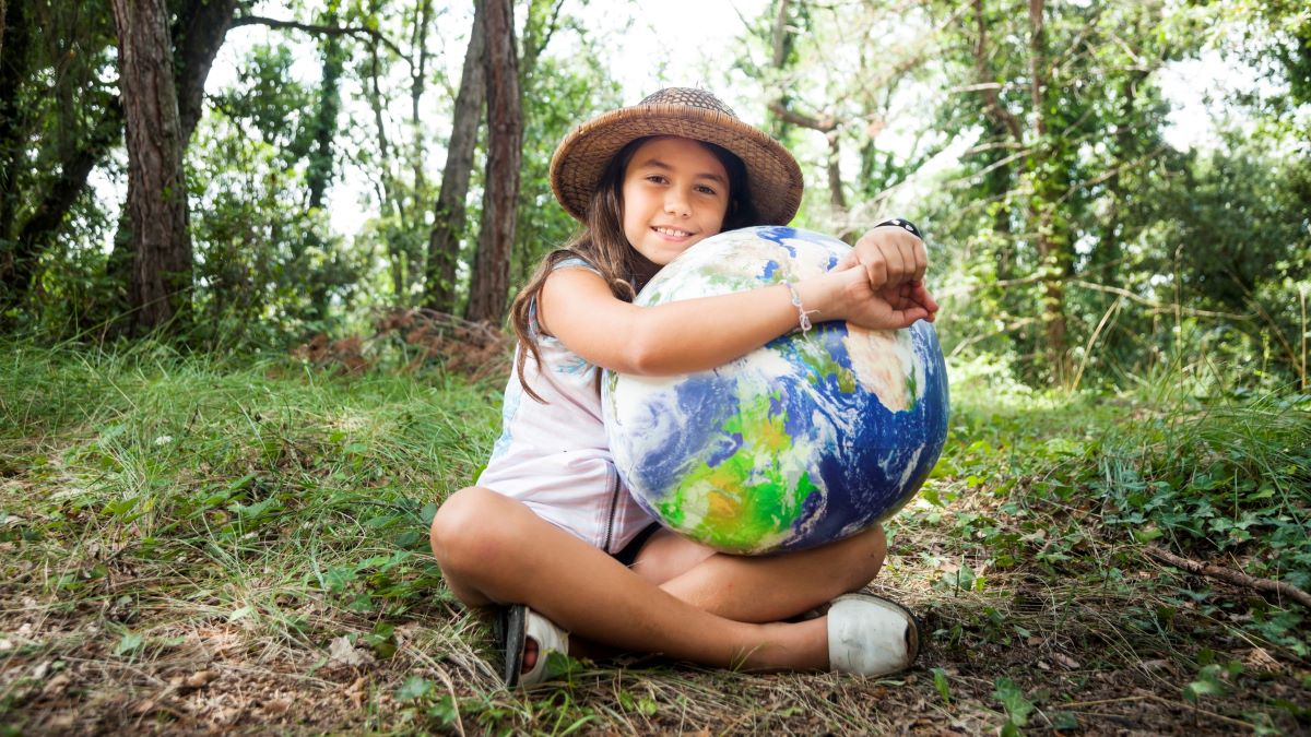 Girl sitting in woodland embracing a representation of the globe