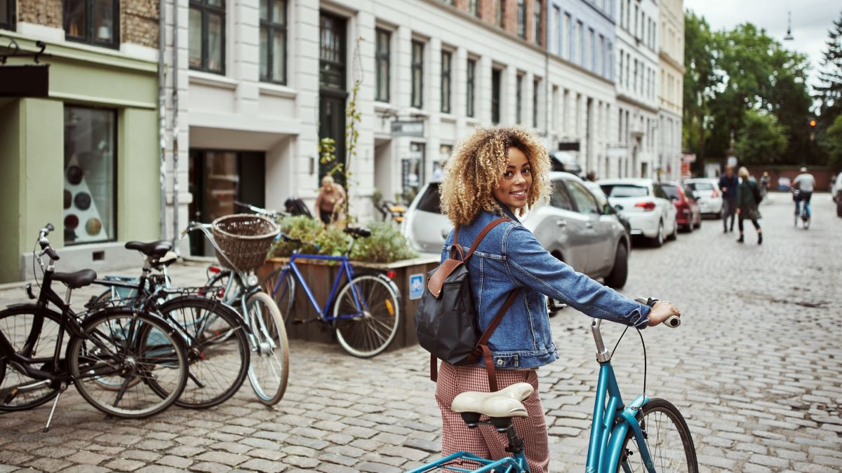 woman with bicycle on cobbled street