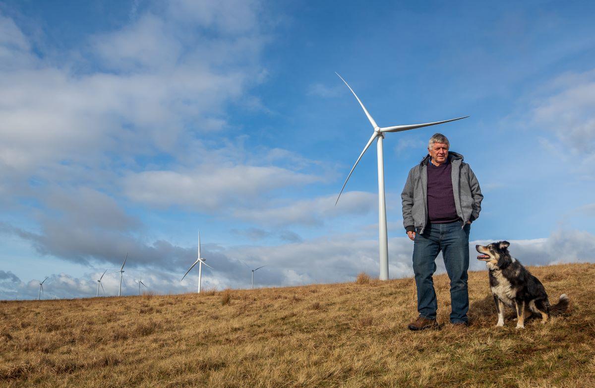 man walking on Welsh moorland with wind turbine in background