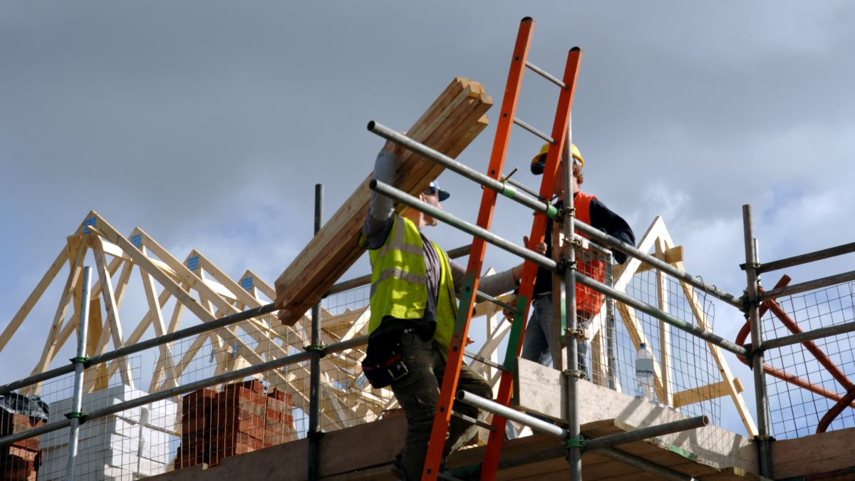 construction workers carrying materials on site