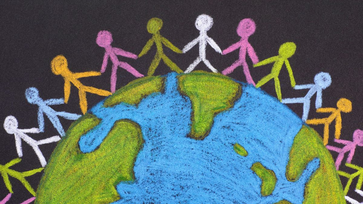 chalk image of the world with people holding hands