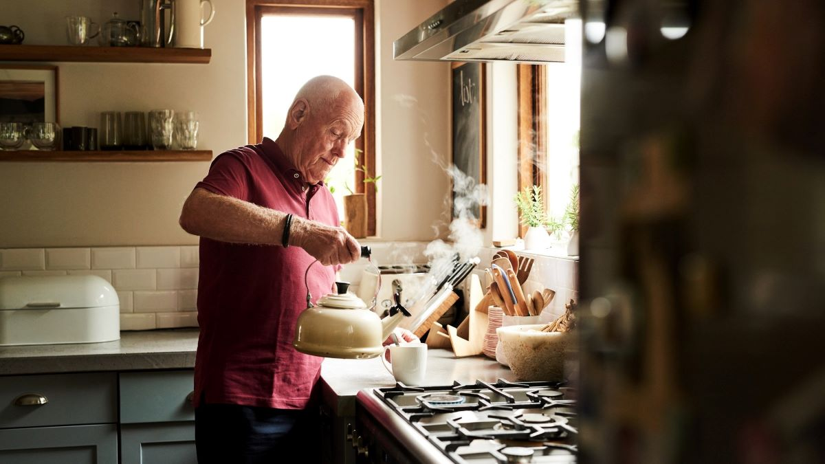 man making a cup of tea in his kitchen