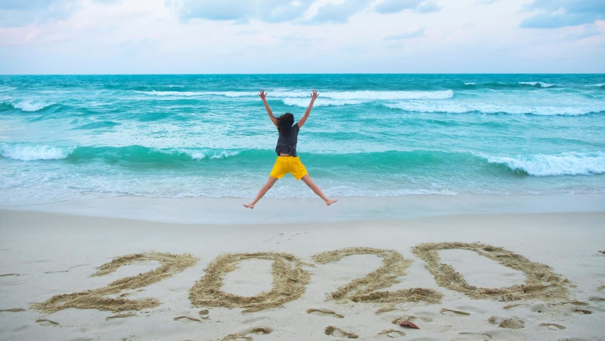 woman jumping in front of the ocean 2020 written in the sand