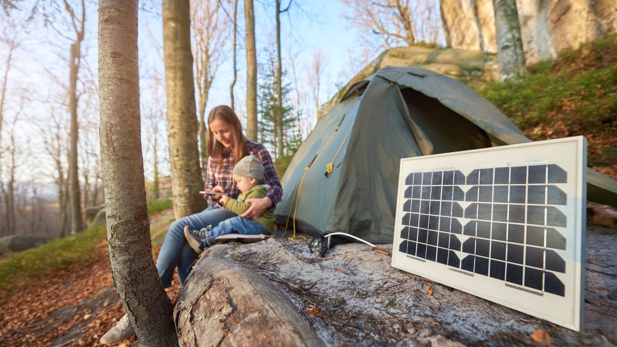 woman sat next to solar panel on a campsite