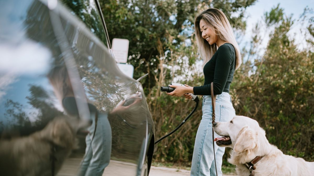 Woman with dog about to plug in her electric car