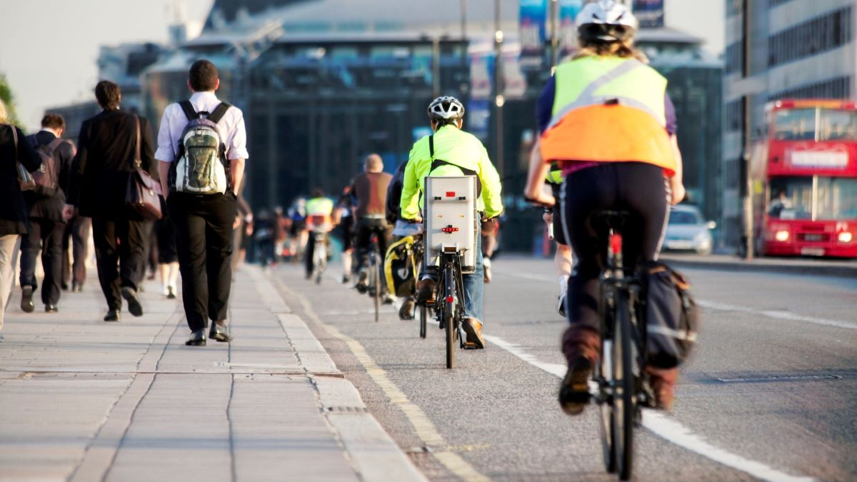 people cycling and walking along a city road