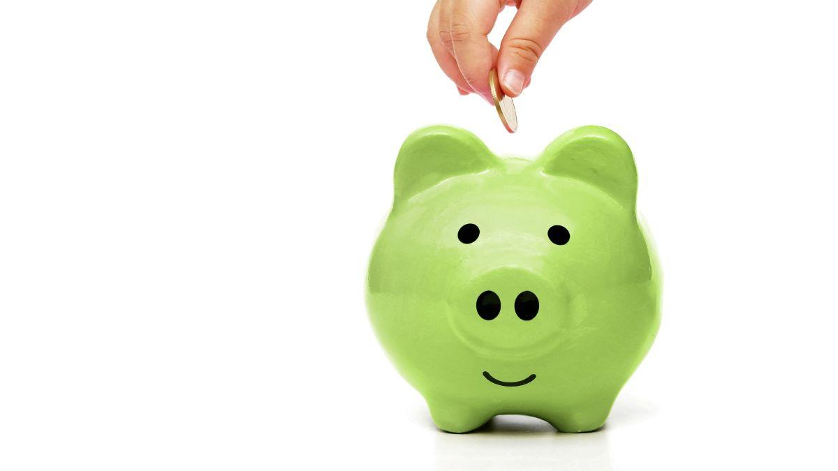 hand putting money into a green piggybank