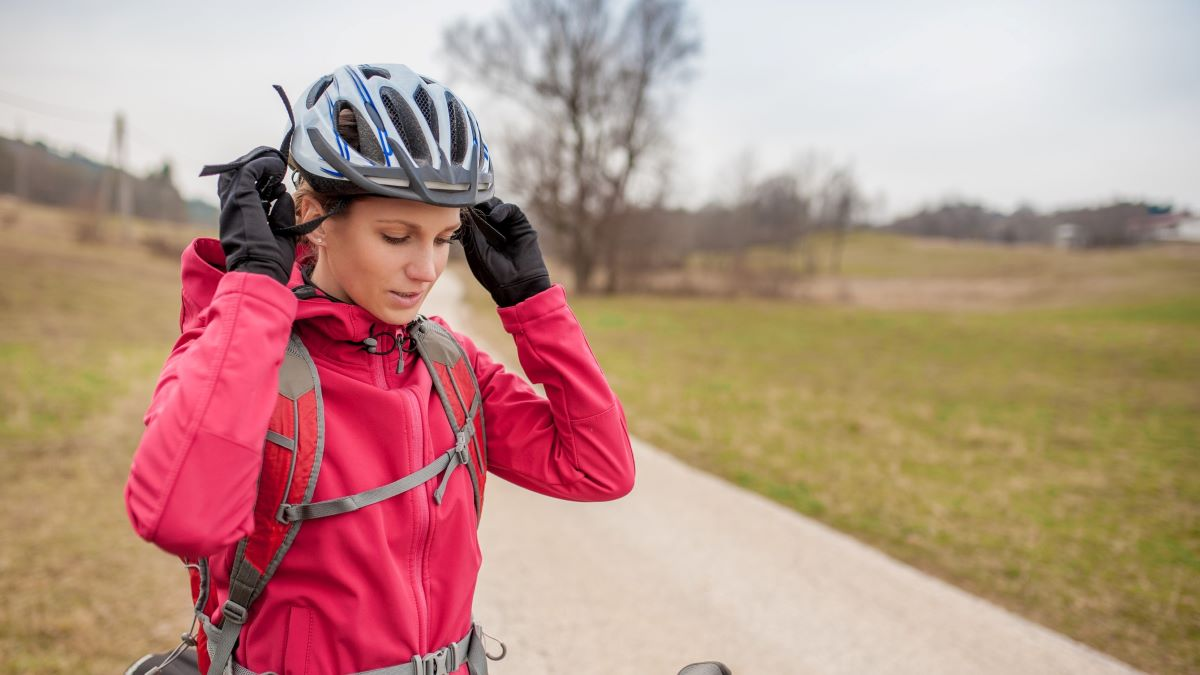female cyclist putting on helmet
