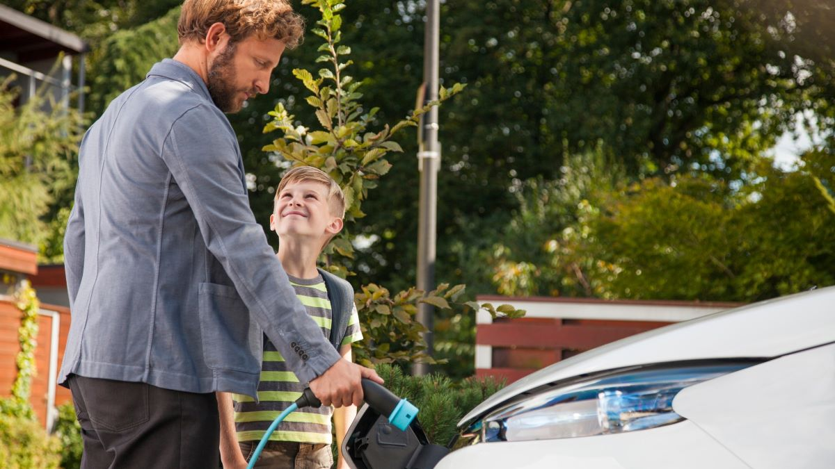 father and son charging electric car