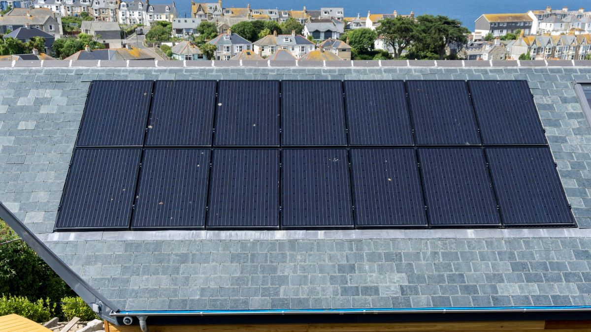 solar panels on grey roof with houses behind
