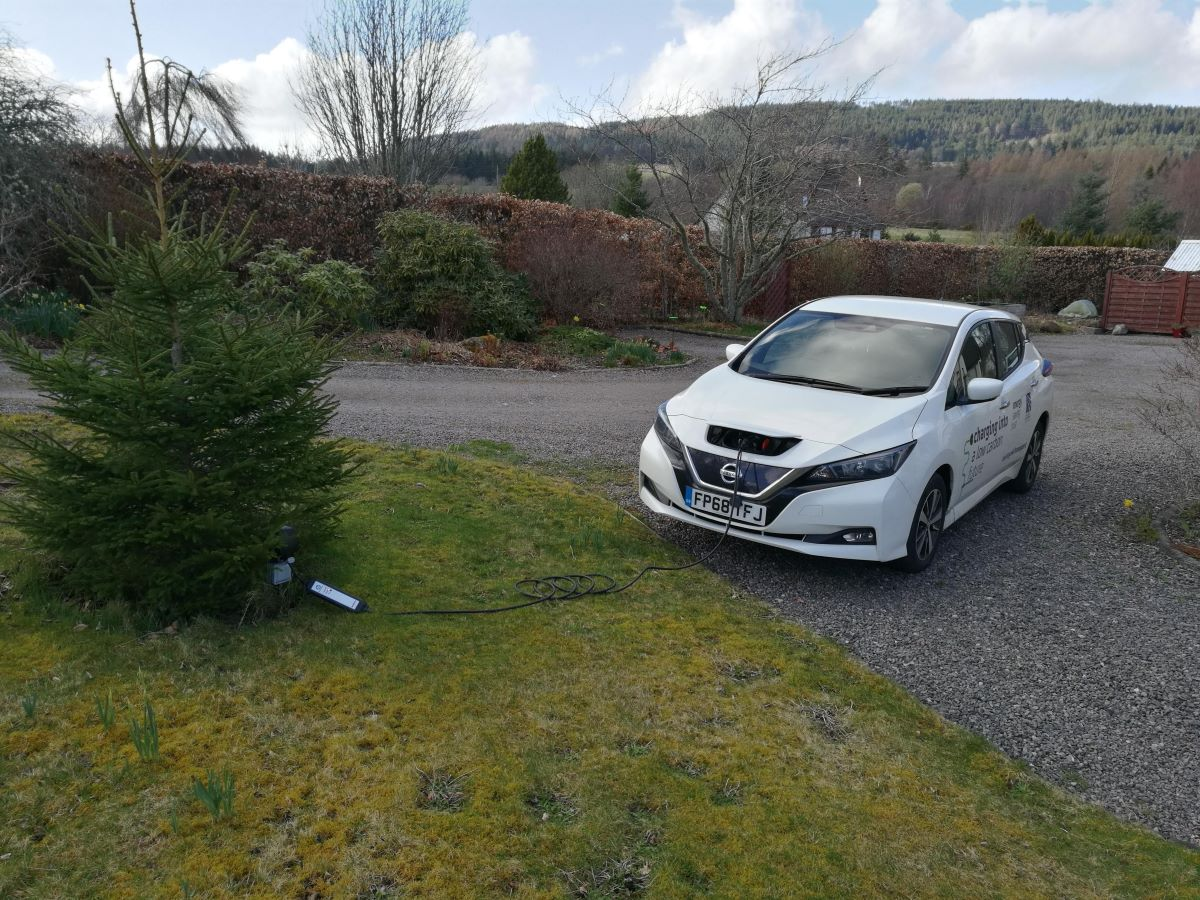 StEVie the EV recharging from a socket by a tree