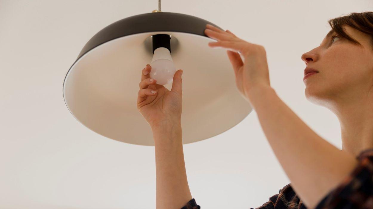 la femme change l'ampoule