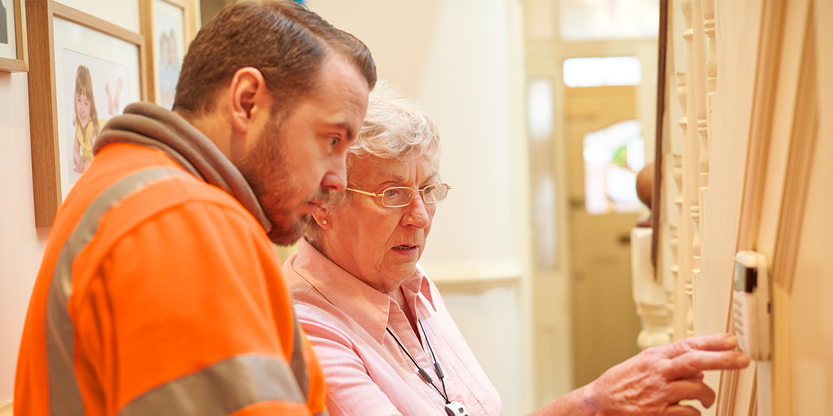 man in high viz showing an older lady a smart meter