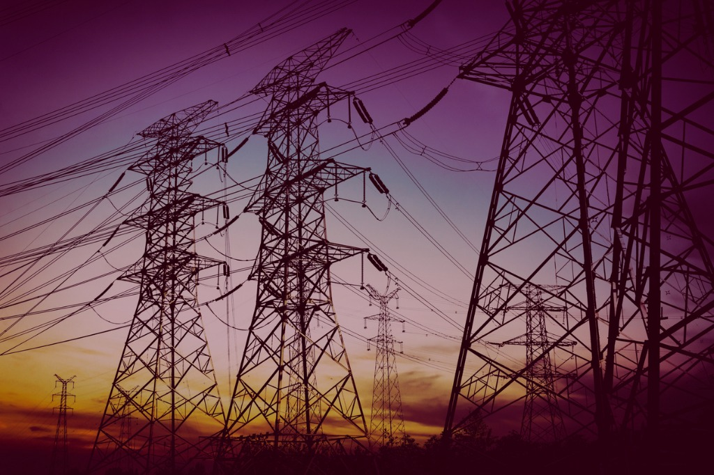 electricity pylons with sunset behind