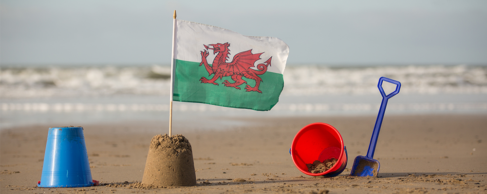 Welsh flag in a sandcastle on a beach with sea in background