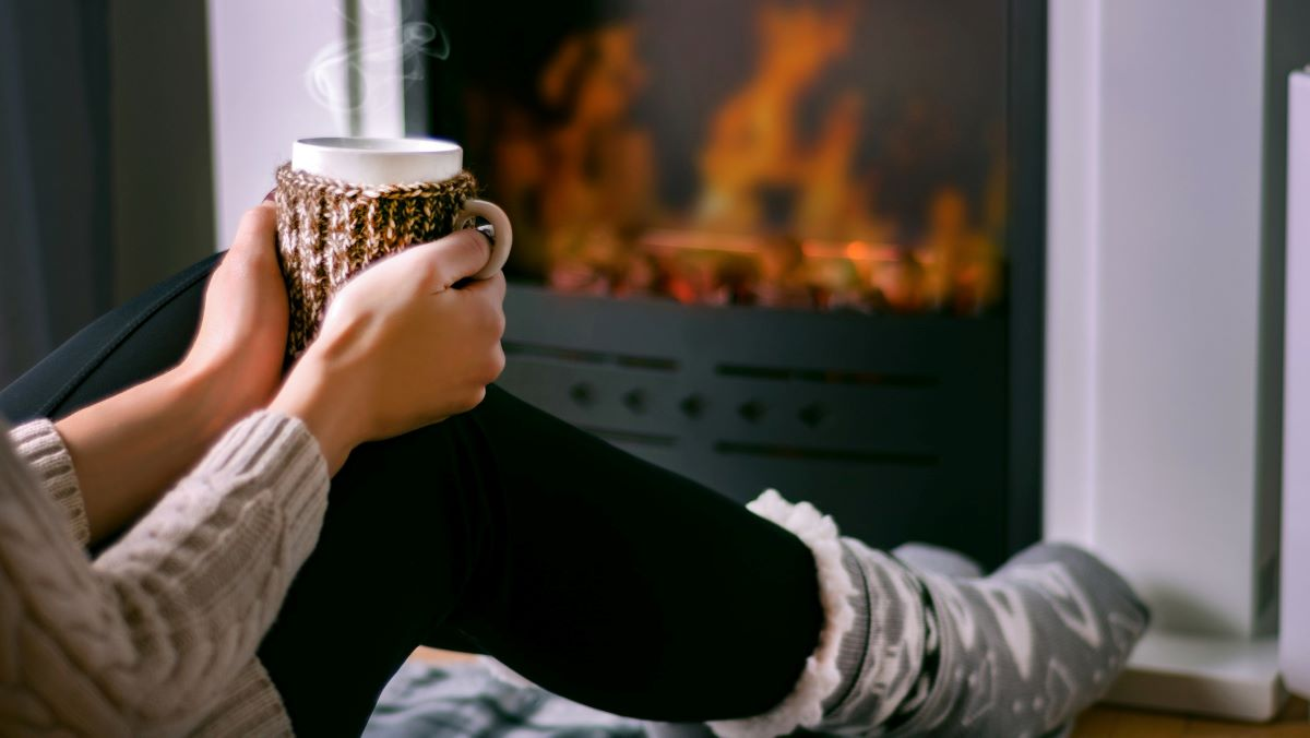 woman sitting by fire with hot drink