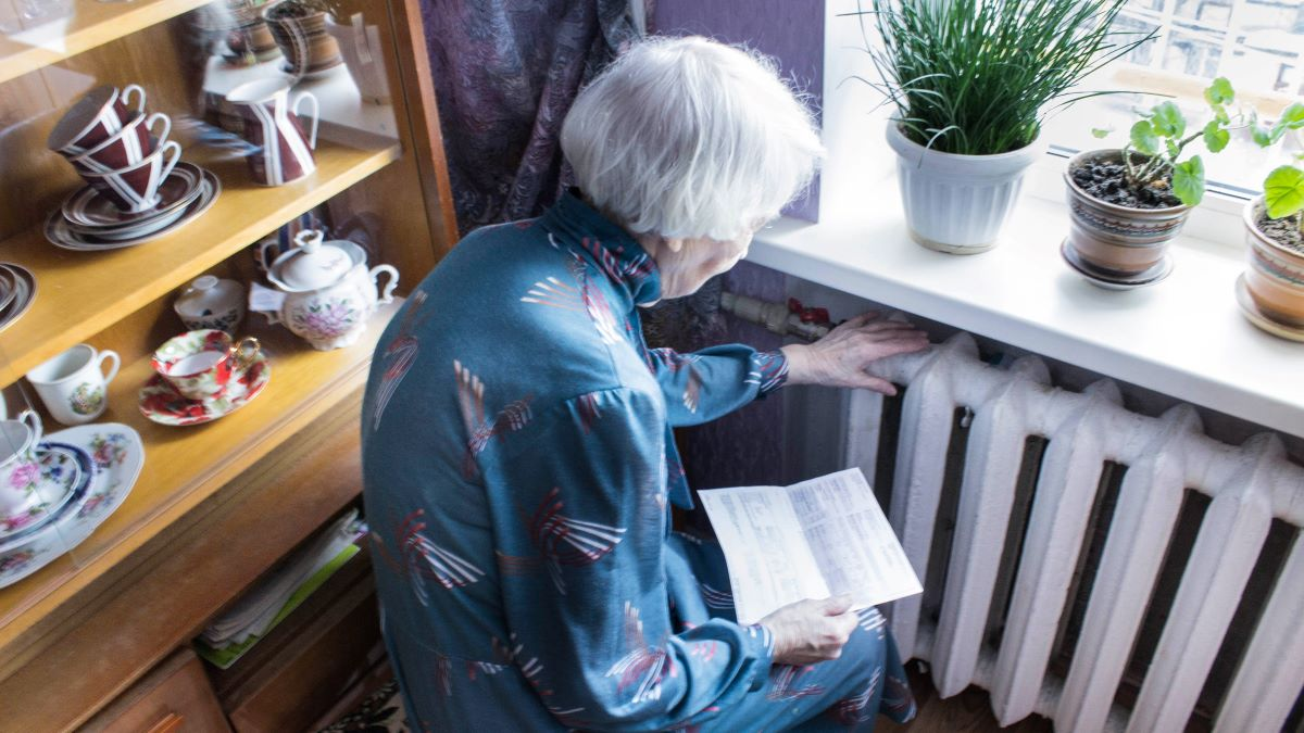 elderly woman sitting beside radiator with electricity bill