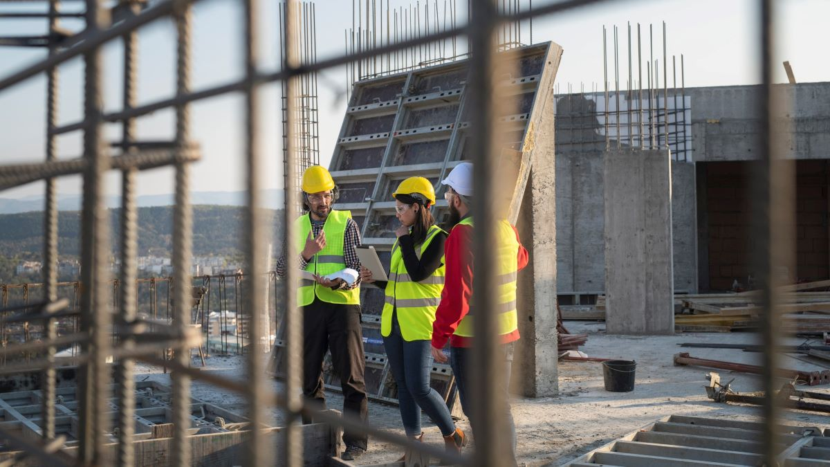 Three people on a construction site