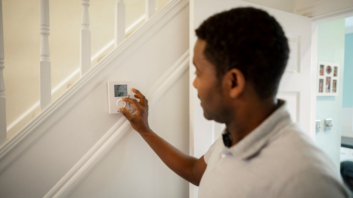 man adjusting thermostat control in home