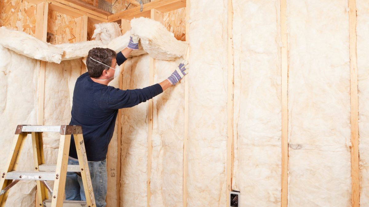 man installing wall insulation on ladder