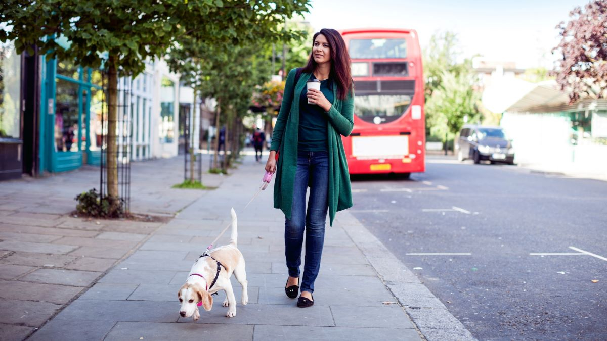 woman walking with dog on pavement
