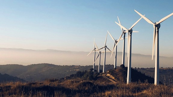 windturbines on hillside with blue sky behind